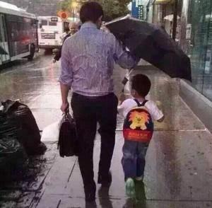 아들에게 우산을 양보하는 아버지